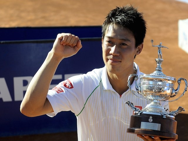 Japanese tennis player Kei Nishikori celebrates his victory with a replica trophy after beating Columbia's Santiago Giraldo during the ATP Final Barcelona on April 27, 2014