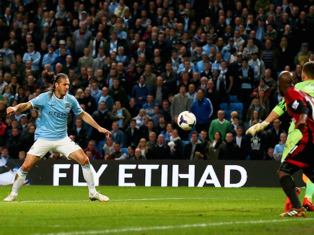 Martin Demichelis of Manchester City (L) scores their third goal past goalkeeper Ben Forster of West Bromwich Albion during the Barclays Premier League match on April 21, 2014