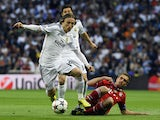 Real Madrid's Croatian midfielder Luka Modric vies with Bayern Munich's defender Philipp Lahm during the UEFA Champions League semifinal first leg at the Santiago Bernabeu stadium in Madrid on April 23, 2014