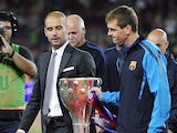 Barcelona's coach Josep Guardiola and second coach Tito Vilanova hold the Spanish league trophy as they celebrate their team's victory in the Spanish League after their Spanish league football match against RC Deportivo de la Coruna at the Camp Nou stadiu