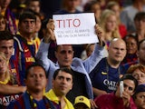 A Barcelona's supporter holds a messae in honour of former coach Tito Vilanova at the end of the Spanish Super Cup second leg football match FC Barcelona vs Atletico Madrid at the Camp Nou stadium in Barcelona on August 28, 2013
