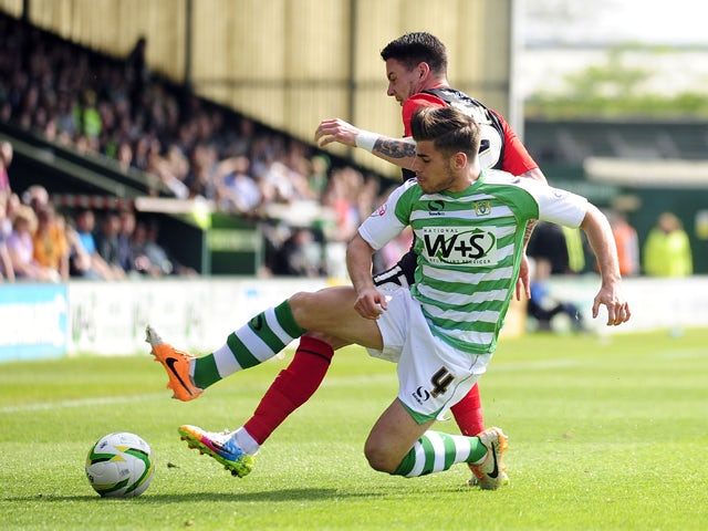 Joe Edwards of Yeovil Town battles for the ball with Adam Hammill of Huddersfield Town during the Sky Bet Championship match between Yeovil Town and Huddersfield Town at Huish Park on April 21, 2014