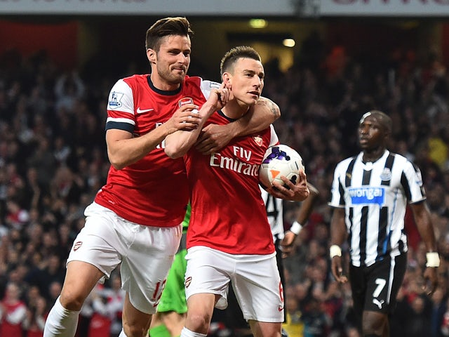 Arsenal's French defender Laurent Koscielny celebrates with Arsenal's French striker Olivier Giroud after he scored his team's opening goal during the English Premier League football match between Arsenal and Newcastle United at the Emirates Stadium in Lo