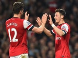 Arsenal's German midfielder Mesut Ozil celebrates with Arsenal's French striker Olivier Giroud after Ozil scored his team's second goal during the English Premier League football match between Arsenal and Newcastle United at the Emirates Stadium in London