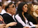 Team owner Donald Sterling of the Los Angeles Clippers and V. Stiviano look on at a basketball game on May 19, 2013