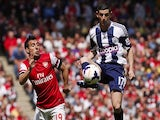 West Bromwich Albion's Graham Dorrans (R) controls the ball as Arsenal's Santi Cazorla (L) chases during the English Premier League football match on May 4, 2014