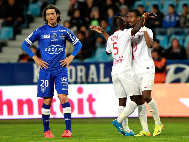 Lille's Ivorian forward Salomon Kalou is congratulated by teammate Senegalese midfielder Idrissa Gueye after scoring a goal as Bastia's French defender Francois Joseph Modesto reacts during the French L1 football match Sporting Club Bastia (SCB) against L