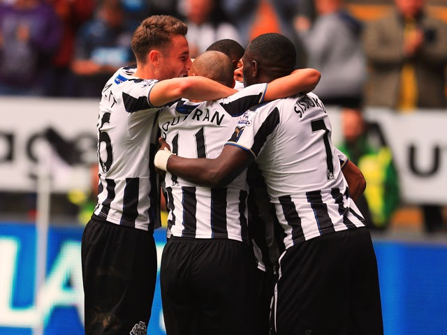 Shola Ameobi of Newcastle United is congratulated by team mates as he scores their first goal with a header during the Barclays Premier League match between Newcastle United and Cardiff City at St James' Park on May 3, 2014