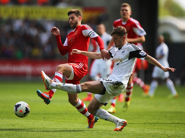 Ben Davies of Swansea City tackles Adam Lallana of Southampton during the Barclays Premier League match between Swansea City and Southampton at Liberty Stadium on May 3, 2014