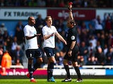 Referee Phil Dowd shows the red card to Younes Kaboul (L) of Spurs as Michael Dawson (C) of Spurs protests during the Barclays Premier League match against West Ham United on May 3, 2014