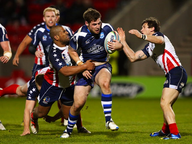 Ben Kavanagh of Scotland is tackled by Eddy Pettybourne of United States during the Rugby League World Cup Inter-Group match between Scotland and United States at AJ Bell Stadium on November 7, 2013