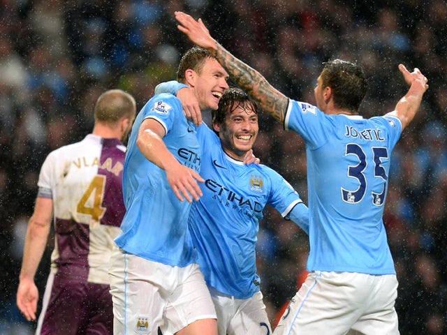 Manchester City's Bosnian striker Edin Dzeko celebrates scoring his second goal with Manchester City's Spanish midfielder David Silva and Manchester City's Montenegrin striker Stevan Jovetic during the English Premier League football match between Manches