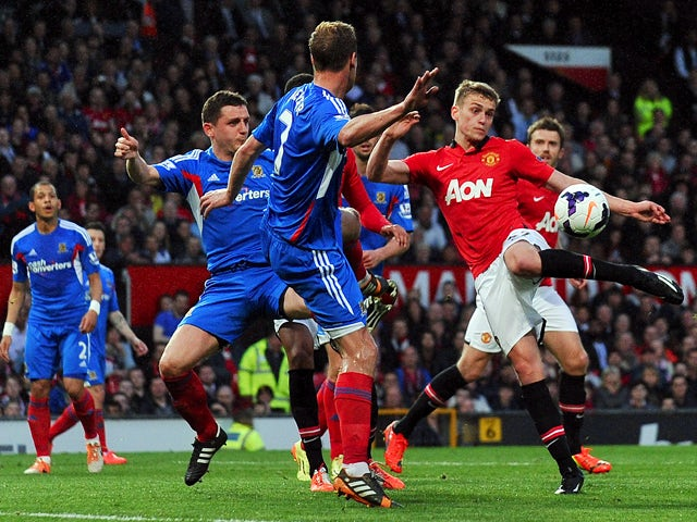 Manchester United's English striker James Wilson shoots to score the opening goal of the English Premier League football match between Manchester United and Hull City at Old Trafford in Manchester, northwest England on May 6, 2014
