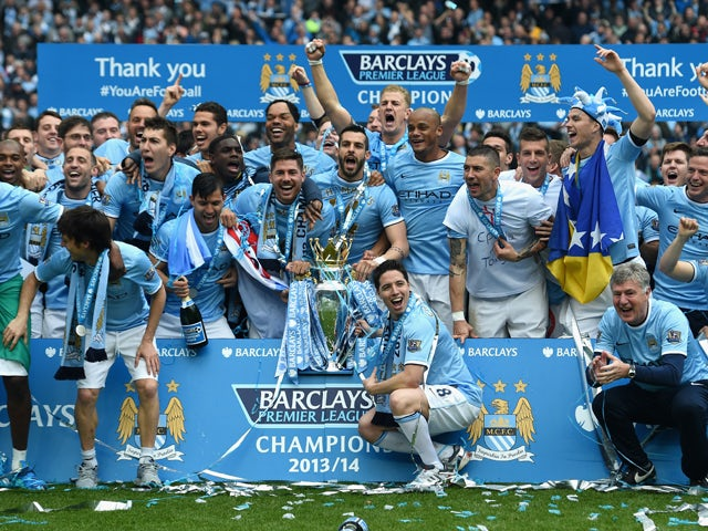 The Manchester City players celebrate with the Premier League trophy at the end of the Barclays Premier League match between Manchester City and West Ham United at the Etihad Stadium on May 11, 2014