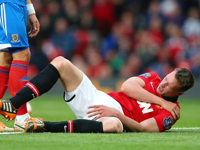 Phil Jones of Manchester United holds his shoulder after sustaining an injury during the Barclays Premier League match between Manchester United and Hull City at Old Trafford on May 6, 2014