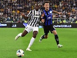 Juventus' French midfielder Paul Labile Pogba (L) fights for the ball with Atalanta's defender Giampaolo Bellini during their Serie A match Juventus vs Atalanta, on May 05, 2014