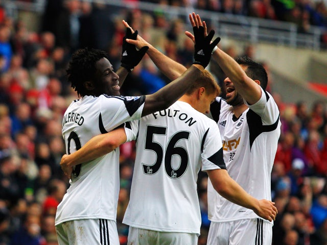 Wilfried Bony of Swansea City celebrates with Jay Fulton and Jordi Amat as he scores their third goal during the Barclays Premier League match between Sunderland and Swansea City at Stadium of Light on May 11, 2014