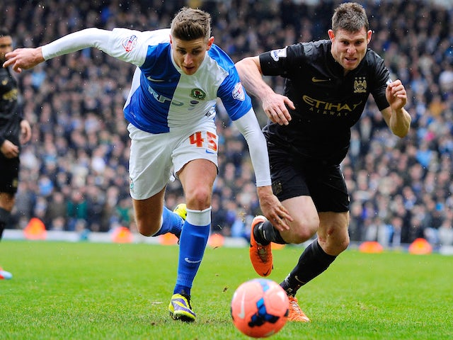 Manchester City midfielder James Milner (R) vies with Blackburn Rovers midfielder Tom Cairney (L) during the FA Cup third round match on January 4, 2014