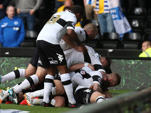 Derby's Will Hughes is mobbed by teammates after scoring the opening goal against Brighton during their play-off semi-final match on May 11, 2014