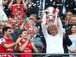 Arsene Wenger manager of Arsenal lifts the trophy in celebration alongside Lukas Podolski, Mikel Arteta and Thomas Vermaelen after the FA Cup with Budweiser Final match between Arsenal and Hull City at Wembley Stadium on May 17, 2014