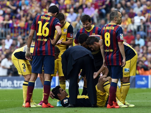Atletico Madrid's Brazilian-born forward Diego da Silva Costa is checked due to a past injury during the Spanish league football match FC Barcelona vs Club Atletico de Madrid at the Camp Nou stadium in Barcelona on May 17, 2014