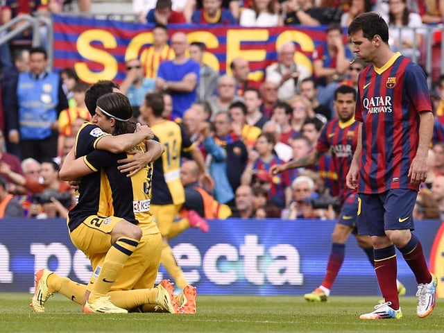 Atletico Madrid's Uruguayan defender Diego Godin celebrates his goal with a teammate during the Spanish league football match FC Barcelona vs Club Atletico de Madrid at the Camp Nou stadium in Barcelona on May 17, 2014