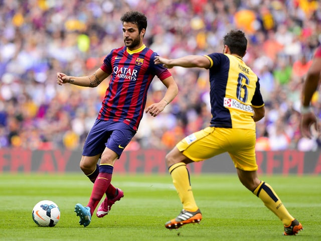 Barcelona's midfielder Cesc Fabregas vies with Atletico Madrid's midfielder Koke during the Spanish league football match FC Barcelona vs Club Atletico de Madrid at the Camp Nou stadium in Barcelona on May 17, 2014