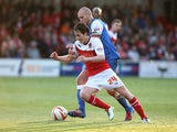 Nigel Penn of York City battles for the ball with Josh Morris of Fleetwood Town during the Sky Bet League Two play off Semi Final second leg match between Fleetwood Town and York City at Highbury Stadium on May 16, 2014