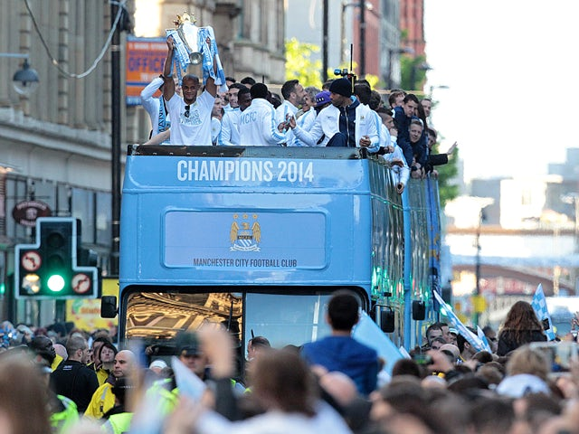 Manchester City's Belgian defender Vincent Kompany holds up the Premiership trophy as the club's players celebrate during a victory parade on an open-topped bus through the streets of Manchester, northwest England, on May 12, 2014