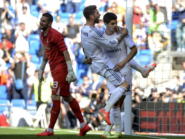 Real Madrid's forward Alvaro Morata celebrates with Real Madrid's defender Sergio Ramos after scoring his team's second goal during the Spanish league football match Real Madrid CF vs RCD Espanyol at the Santiago Bernabeu stadium in Madrid on May 17, 2014