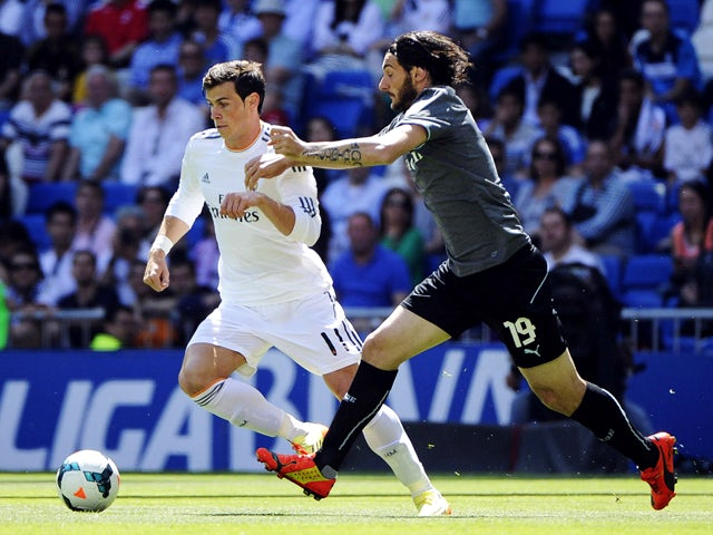 Real Madrid's Welsh forward Gareth Bale vies with Espanyol's Argentinian defender Diego Colotto during the Spanish league football match Real Madrid CF vs RCD Espanyol at the Santiago Bernabeu stadium in Madrid on May 17, 2014