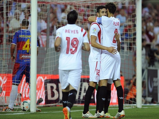 Sevilla's midfielder Vicente Iborra de la Fuente (C) celebrates with Sevilla's Argentinian defender Federico Fazio after scoring during the Spanish league football match against Elche on May 18, 2014
