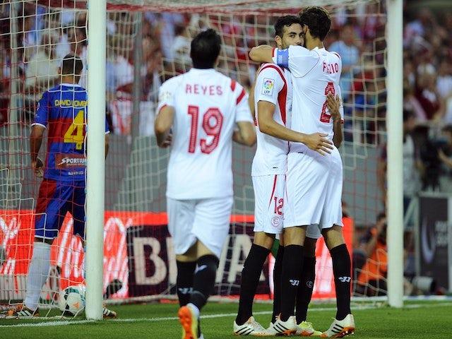 Sevilla's midfielder Vicente Iborra de la Fuente (C) celebrates with Sevilla's Argentinian defender Federico Fazio after scoring during the Spanish league football match against Elche on May 18, 2014