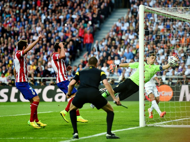Iker Casillas of Real Madrid fails to stop the ball headed in by Diego Godin of Club Atletico de Madrid (not pictured) for the first goal during the UEFA Champions League Final between Real Madrid and Atletico de Madrid at Estadio da Luz on May 24, 2014