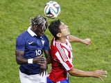 France's defender Bacary Sagna (L) vies with Paraguay's forward Roque Santa Cruz (R) during their international friendly football match France vs Paraguay, on June 01, 2014