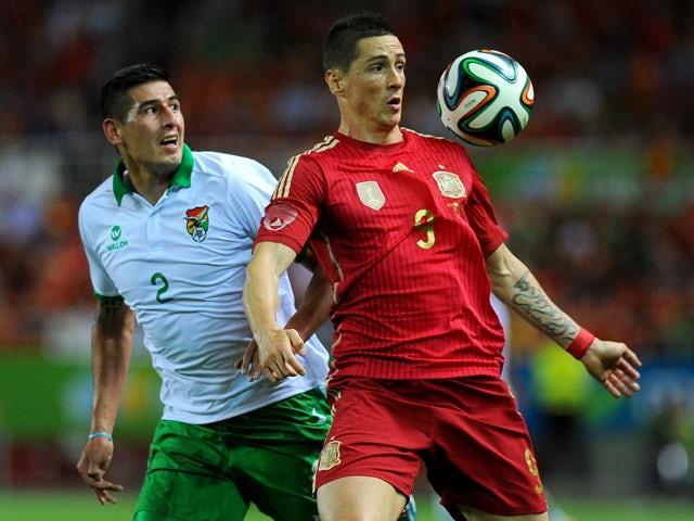 Bolivia's defender Ronald Eguino vies with Spain's forward Fernando Torres during the international friendly football match Spain vs Bolivia at the Ramon Sanchez Pizjuan stadium in Sevilla on May 30, 2014