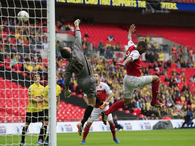 The ball goes over Burton Albion's English goalkeeper Dean Lyness (L) during the English League 2 Play-Off final football match between Burton Albion and Fleetwood Town on May 26, 2014