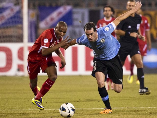 Uruguay defender Diego Godin battles for possession on November 13, 2013.