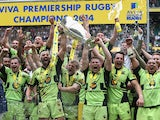 Northampton Saints team captain Dyland Hartley (R) and match captain Tom Wood raise the trophy after their victory during the Aviva Premiership Final between Saracens and Northampton Saints at Twickenham Stadium on May 31, 2014