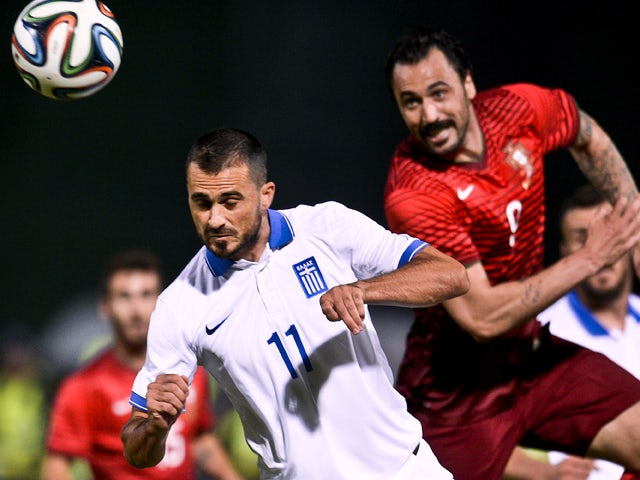 Portugal's forward Hugo Almeida vies with Greece's defender Loukas Vyntra (L) during the friendly football match Portugal vs Greece at the Jamor National stadium in Oeiras on the outskirts of Lisbon on May 31, 2014