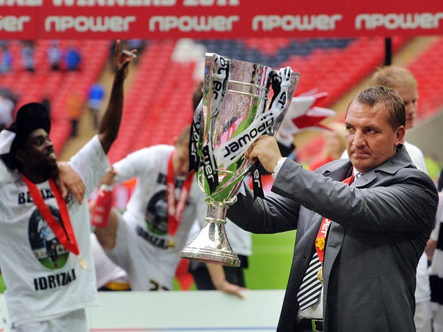 Swansea City's manager Brendan Rodgers celebrates with the trophy after his team beat Reading during the 2011 Championship play-off final football match at Wembley Stadium in London on May 30, 2011