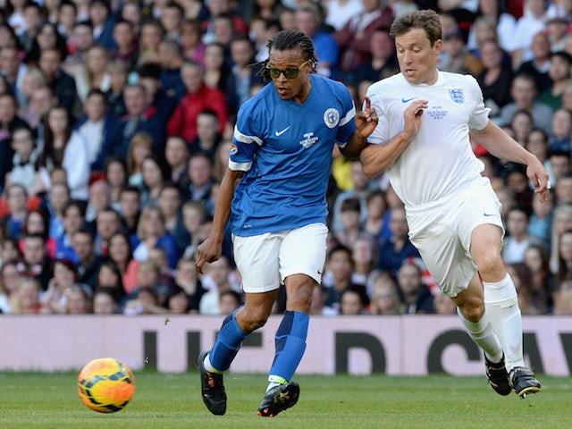 Edgar Davids of the Rest of the World is closed down by Ben Shephard of England during Soccer Aid 2014 at Old Trafford on June 8, 2014