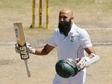 Hashim Amla of South Africa celebrates reaching 100 runs during day four of the second Test against Australia in Port Elizabeth on February 23, 2014