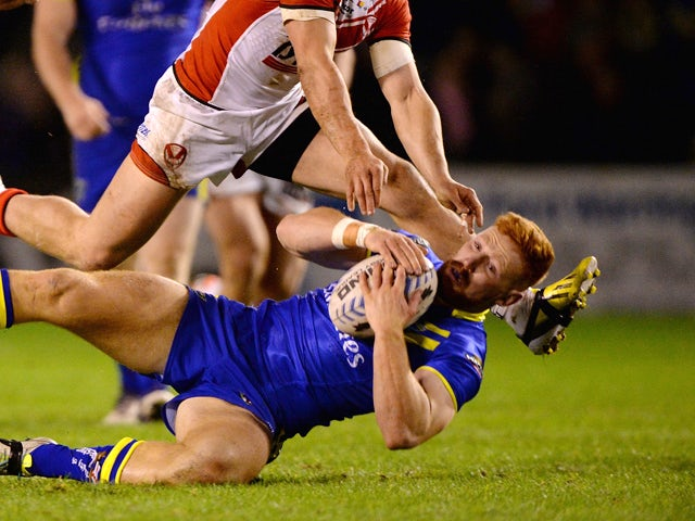 James Laithwaite of Warrington Wolves is tackled during the Super League match between Warrington Wolves and St Helens at The Halliwell Jones Stadium on February 13, 2014
