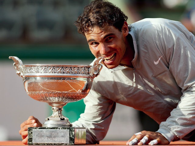 Rafael Nadal of Spain bites the Coupe de Mousquetaires after victory in his men's singles final match against Novak Djokovic on June 8, 2014