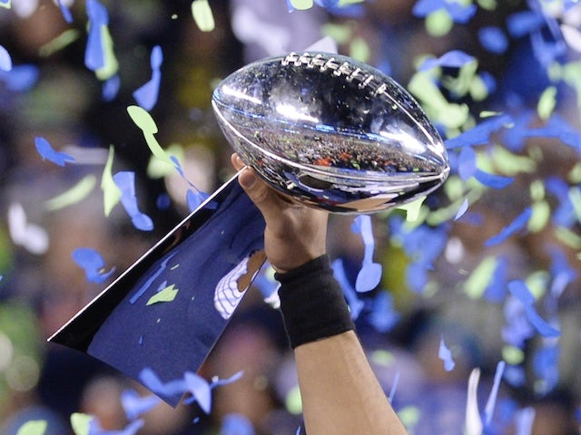 Quarterback Russell Wilson of the Seattle Seahawks holds the Vince Lombardi Trophy following victory over the Denver Broncos on February 2, 2014