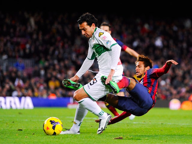 Neymar of FC Barcelona is brought down by Sergio Mantecon of Elche FC during the La Liga match between FC Barcelona and Elche FC at Camp Nou on January 5, 2014