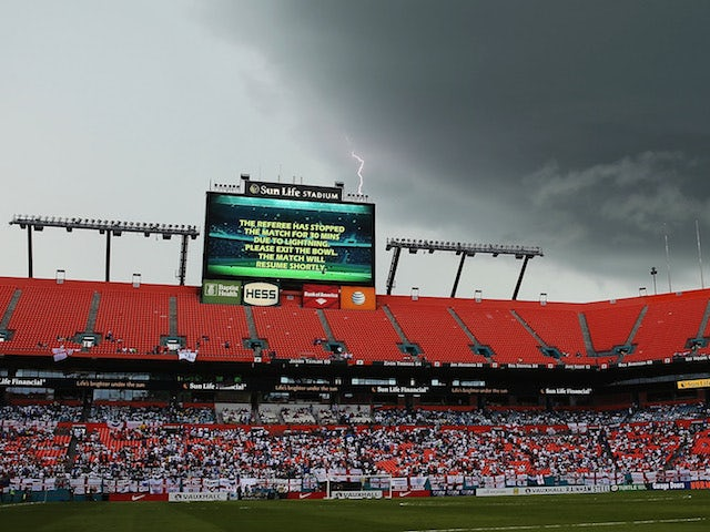 Lightning strikes behind the scoreboard as the match is delayed due to inclement weather during the International Friendly match between England and Honduras on June 7, 2014