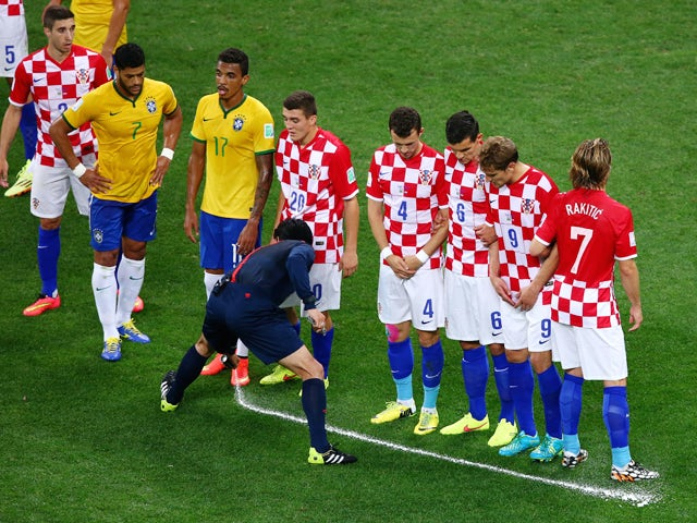 Referee Yuichi Nishimura sprays a temporary line on the field marking ten yards as players from Brazil and Croatia form a wall during the 2014 FIFA World Cup Brazil Group A match between Brazil and Croatia at Arena de Sao Paulo on June 12, 2014