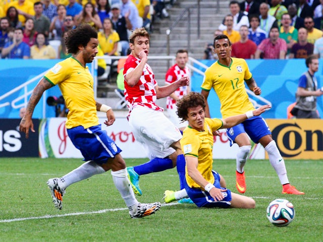Marcelo and David Luiz of Brazil watch as a ball is deflected into the net in the first half during the 2014 FIFA World Cup Brazil Group A match between Brazil and Croatia at Arena de Sao Paulo on June 12, 2014